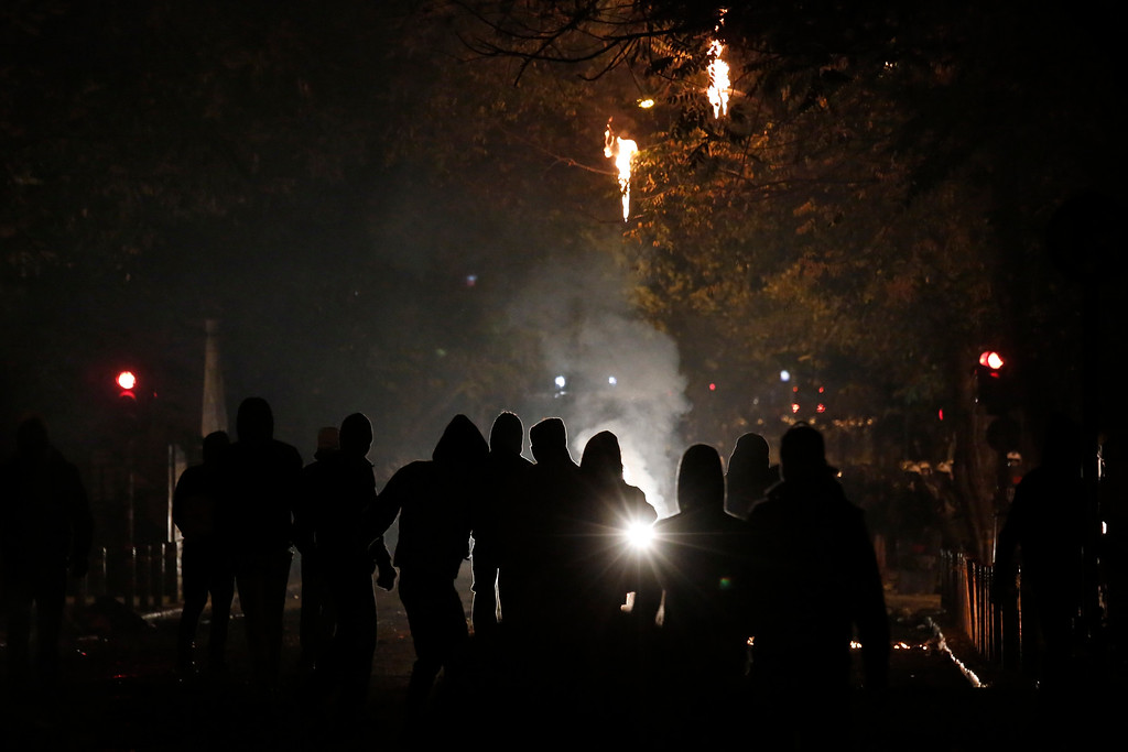 . Protesters are silhouetted by the lights of a water canon during riots in Athens neighborhood of Exarchia, a haven for extreme leftists and anarchists, on Saturday, Dec. 6, 2014. (AP Photo/Kostas Tsironis)