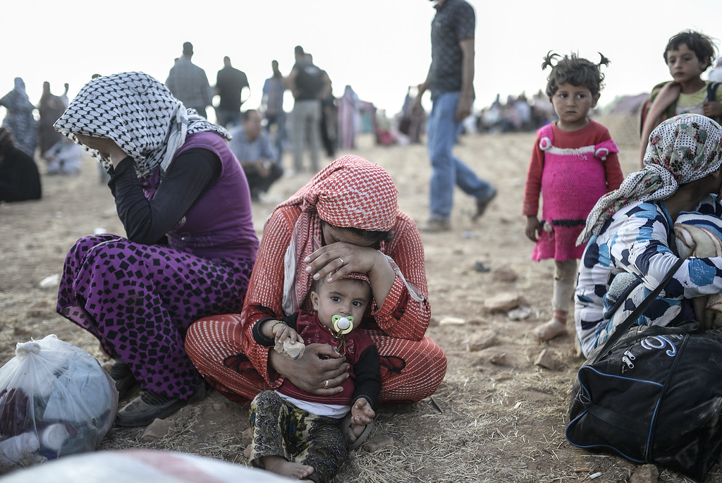 . Syrian Kurds wait near Syria border at  the southeastern town of Suruc in Sanliurfa province, on September 20, 2014. Tens of thousands of Syrian Kurds flooded into Turkey on Saturday, fleeing an onslaught by the jihadist Islamic State group that prompted an appeal for international intervention.  BULENT KILIC/AFP/Getty Images