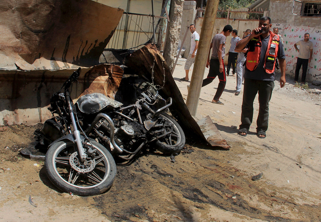 . A Palestinian medic inspects the wreckage of a motorcycle caused by an Israeli airstrike in Rafah on Thursday, July 31, 2014. Fadel Elmeghary, an Islamic Jihad member, was killed in the airstrike, while on his motorcycle in Rafah, according to Gaza health official Ashraf al-Kidra. (AP Photo/Hatem Ali)