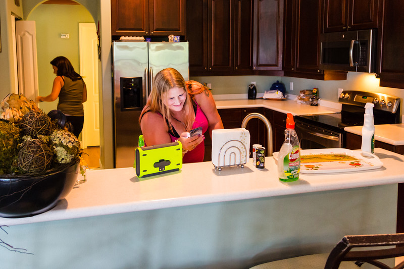"""Tabitha Franks, 31, of Loxahatchee, Florida, loads up the Pandora™ music app on her iPhone™ to listen to music while cleaning the kitchen at the All About Recovery younger women's sober home in Loxahatchee, Florida on Friday, June 24, 2016. Residents are required to keep the sober home clean, but once a week, the residents  are assigned an area of the sober house to """"deep clean"""". (Joseph Forzano / The Palm Beach Post)"""