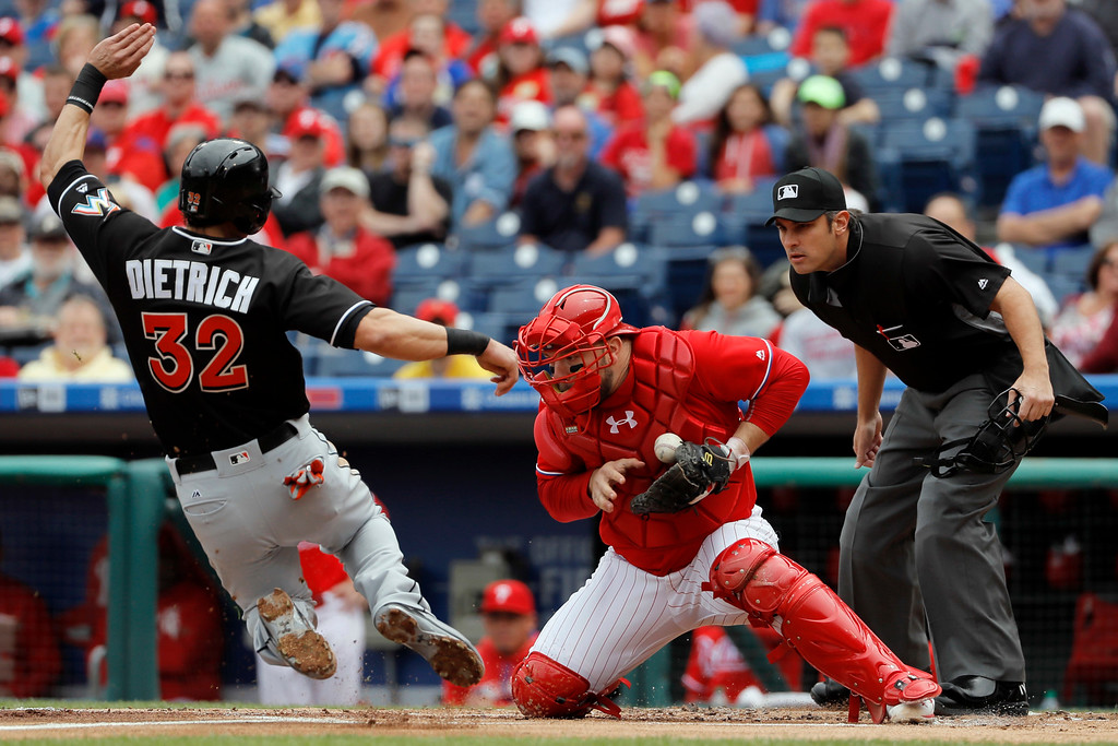 . Miami Marlins\' Derek Dietrich, left, scores past Philadelphia Phillies catcher Cameron Rupp, center, on a double by Christian Yelich during the first inning of a baseball game, Wednesday, May 18, 2016, in Philadelphia. Yelich advanced to third on the throw home. (AP Photo/Matt Slocum)