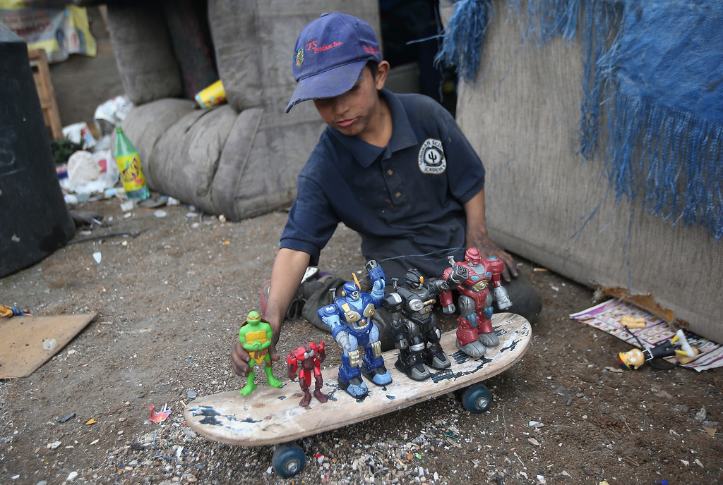 . NOGALES, MEXICO - MARCH 05:  Carlos Roman, 9, plays with toys found at the Tirabichi garbage dump on March 5, 2013 in Nogales, Mexico. About 30 families live at the landfill, searching for recyclables to sell for a living. Many have received protective gloves from the nearby non-profit Home of Hope and Peace, which plans to expand its assistance to Tirabichi residents.  (Photo by John Moore/Getty Images)
