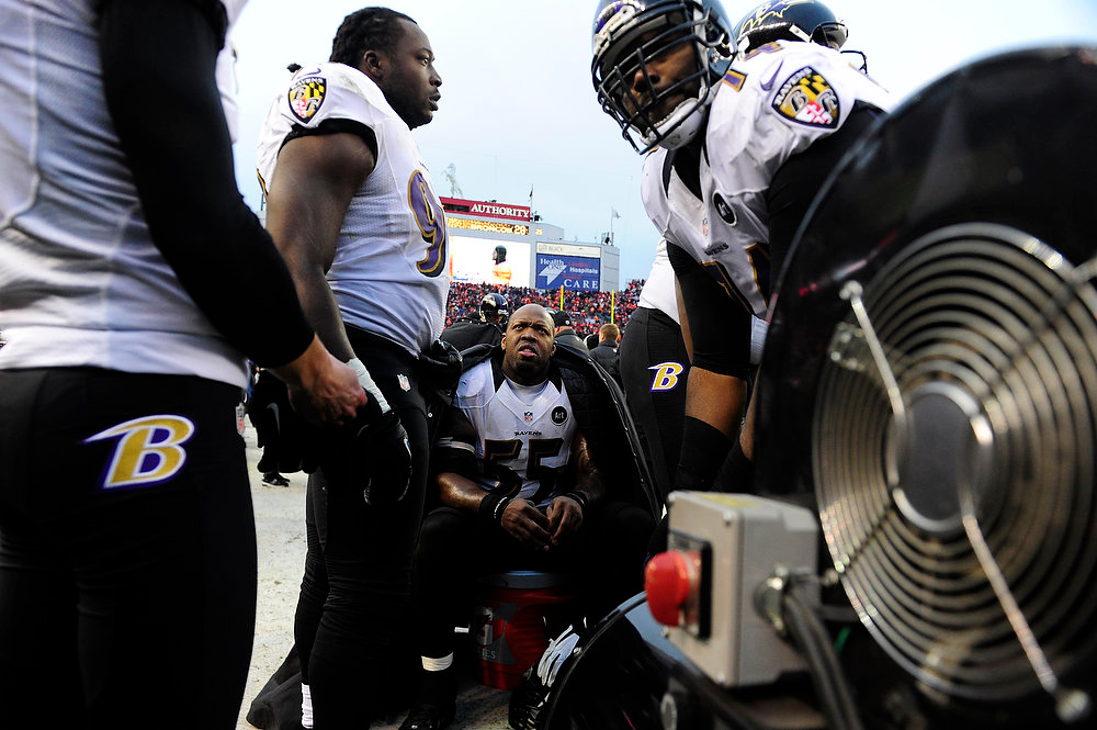 Description of . Baltimore Ravens outside linebacker Terrell Suggs (55) and other Ravens players try to keep warm on the sidelines. The Denver Broncos vs Baltimore Ravens AFC Divisional playoff game at Sports Authority Field Saturday January 12, 2013. (Photo by AAron  Ontiveroz,/The Denver Post)