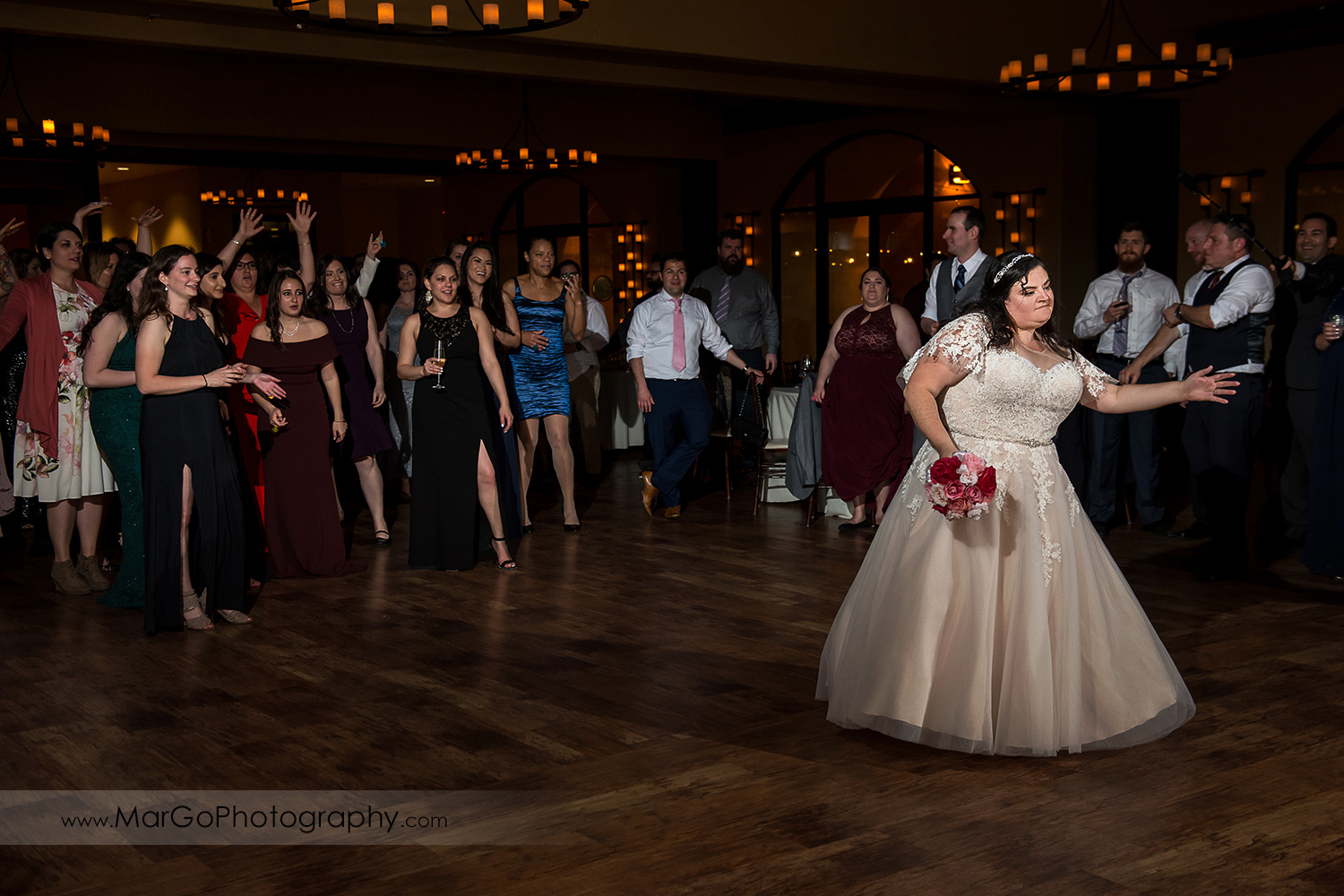 bride tossing the bouquet during wedding reception at Livermore Garre Vineyard and Winery