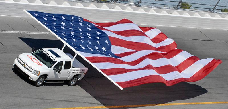 . A large American flag is pulled around Turn 4 prior to the start of the Daytona 500 at Daytona International Speedway in Daytona Beach, Fla., Sunday, Feb. 18, 2007. (AP Photo/Paul Kizzle)