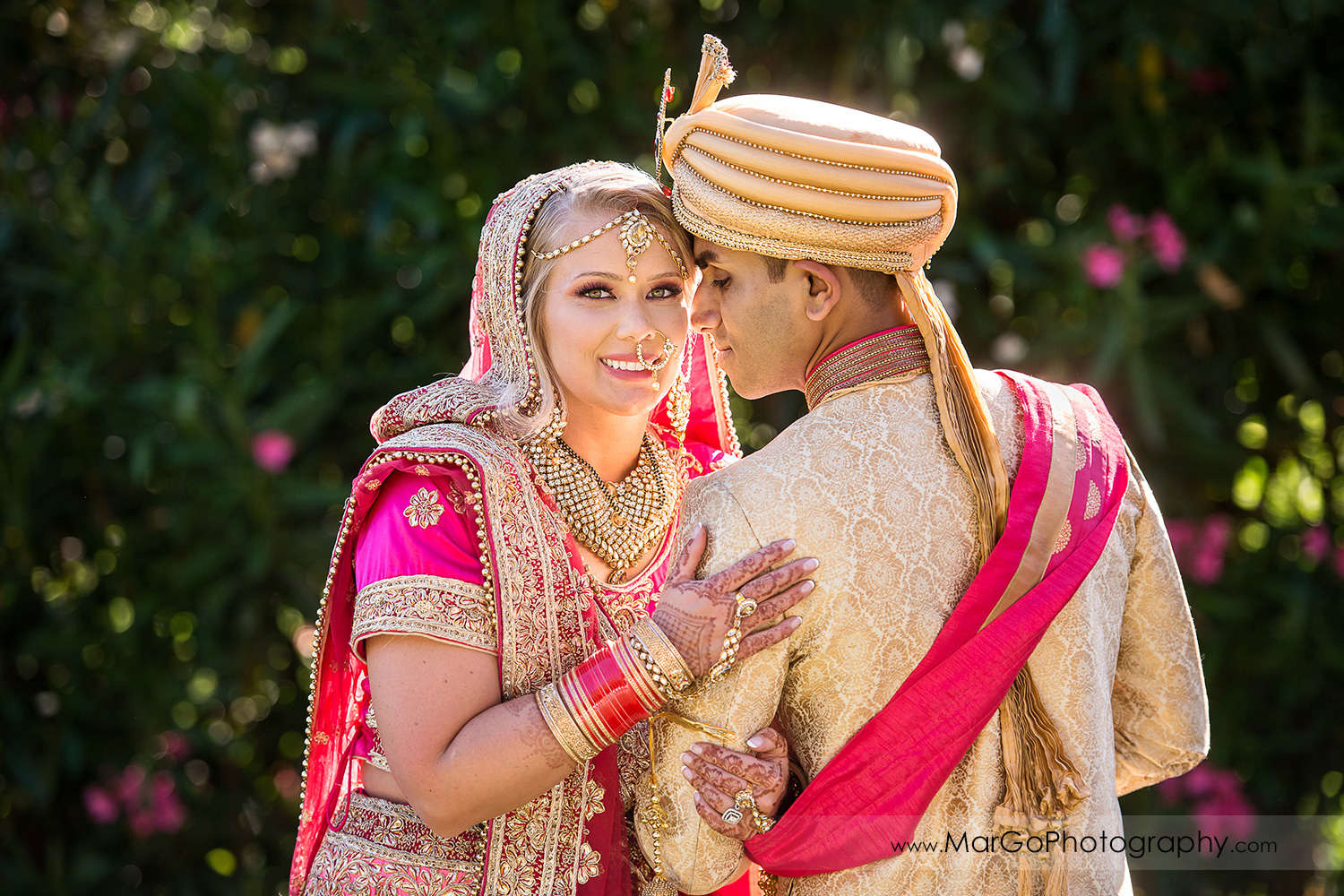 Indian bride and groom in pink and golden outfits on the wall of white and pink flowers at Elliston Vineyards in Sunol