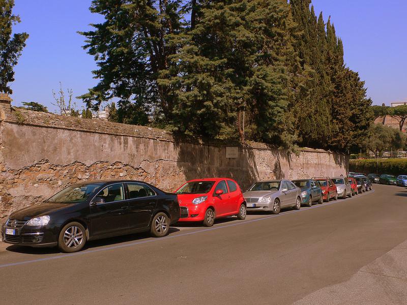 Roman streetscape : Cars line an crumbling wall blanketing the sides of the Via di Santa Sabina.