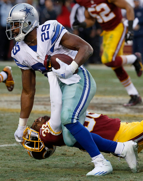 . Dallas Cowboys running back DeMarco Murray (29) pushes Washington Redskins cornerback Justin Rogers to the turf during the second half of an NFL football game in Landover, Md., Sunday, Dec. 28, 2014. The Cowboys defeated the Redskins 44-17. (AP Photo/Alex Brandon)