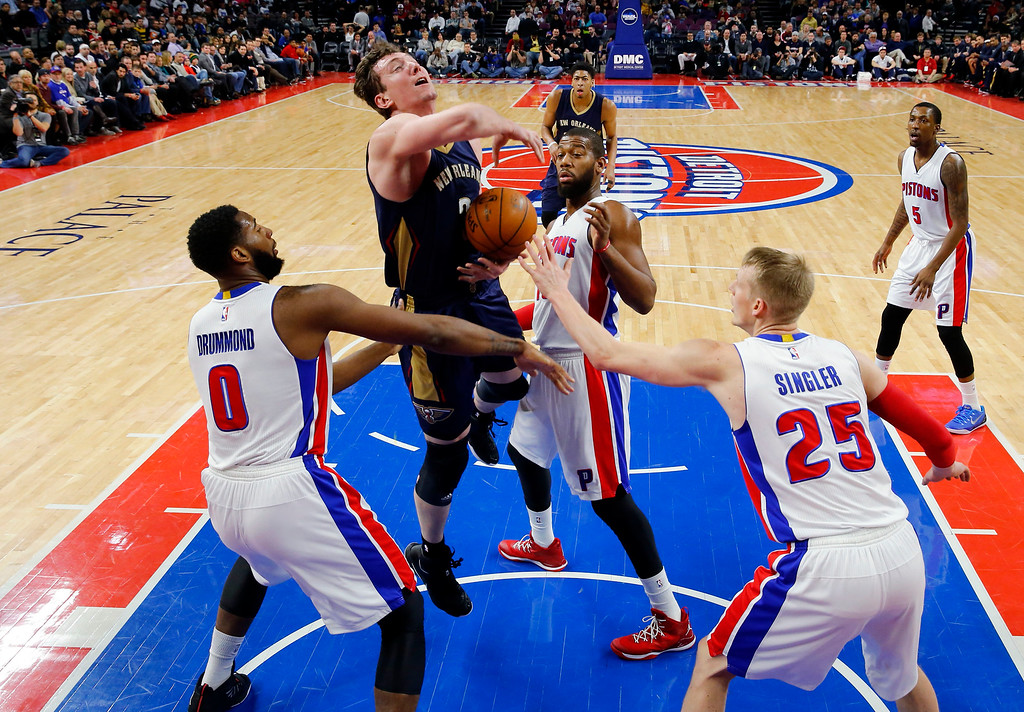 . New Orleans Pelicans center Omer Asik (3) loses the ball between Detroit Pistons center Andre Drummond (0), forward Greg Monroe (10) and forward Kyle Singler (25) during the first half of an NBA basketball game in Auburn Hills, Mich., Wednesday, Jan. 14, 2015. (AP Photo/Paul Sancya)