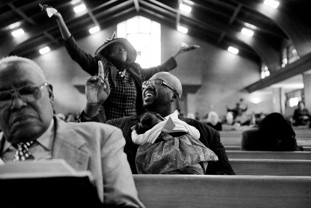 Description of . DENVER, CO - NOVEMBER 24: Pastor Victor-Lamonte Lane sings along with fellow parishioners while holding his daughter Abigail. Lane was installed as the new pastor of the historic Northeast Park Hill church. Most Sundays during the fall and winter, I am shooting Nuggets, Avalanche or the Broncos. This Sunday, however, I had an opening and received this assignment. I really loved it. The congregation was awesome. One of my favorite shoots of the year. (Photo by AAron Ontiveroz/The Denver Post)