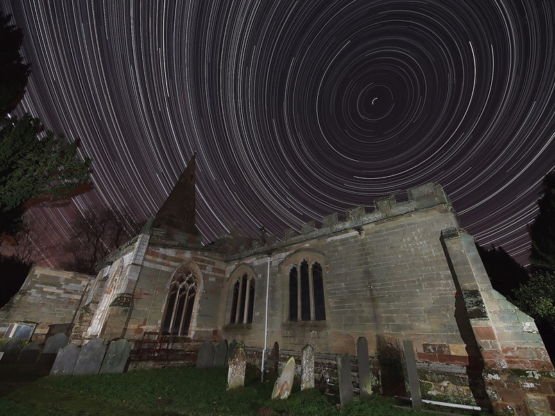 Dec 01/02 2012.  Clear skies at last for the first serious frost of winter. Temps got down -4C here in the East Midlands. Returning to a favourite local landmark, Misterton church nr Lutterworth, Leics. A great foreground composition subject for this star trail. I set up the Olympus E5 with 7-14mm wide angle lens on tripod at F4, ISO 500 and 15s exposure time. Attaching the RM-CB1 cable I locked the cable to take continuous shots all night. Camera was in place approx 1800hrs and I picked it up the following morning at approx 0630hrs. 12 hours of continuous shooting, only made possible by using the DIY dew shield which prevented the camera lens from freezing over. I imported the 2000+ images into StarStax software to provide the final stacked composite. The stars are spinning around the celestial north star (polaris) top right and on the left the stars start to reverse direction. This is the celestial equator. 91% waning moon too!