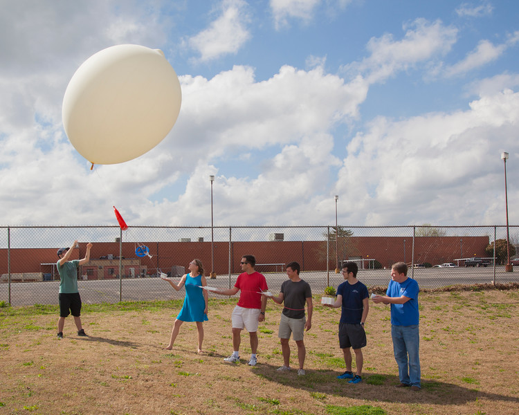 Liftoff!  The radiosonde comparison balloon is released.  Each person in the photo is ready to release their respective instruments in turn as the balloon ascends.