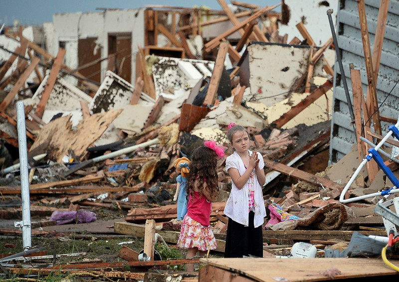 . Two girls stand in rubble after a tornado struck Moore, Oklahoma, May 20, 2013. A 2-mile-wide (3-km-wide) tornado tore through the Oklahoma City suburb of Moore on Monday, killing at least 51 people while destroying entire tracts of homes, piling cars atop one another, and trapping two dozen school children beneath rubble. REUTERS/Gene Blevins