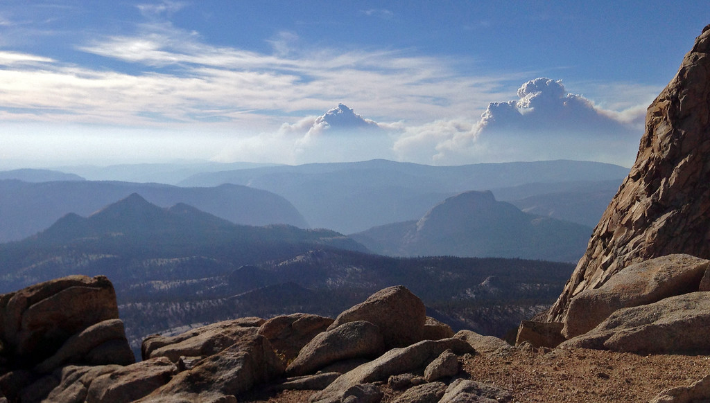 . Smoke clouds and bands of haze from the Rim Fire in the western Sierra Nevada loom up some 20 miles behind the famed granite monolith known as Half Dome, right center, seen from 11,500-foot Mt. Clark in Yosemite Valley in Yosemite National Park, Calif., Saturday, Aug. 24, 2013. Crews working to contain one of California\'s largest-ever wildfires gained some ground Monday against the flames threatening San Francisco\'s water supply, several towns near Yosemite National Park and historic giant sequoias. Containment of the Rim Fire more than doubled to 15 percent, although it was within a mile of the park\'s Hetch Hetchy Reservoir, the source of San Francisco\'s famously pure drinking water, officials said Monday. (AP Photo/Tami Abdollah)