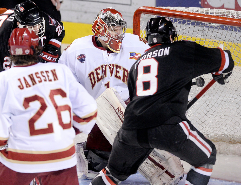 . DENVER, CO. - JANUARY 10: St. Cloud State center Cory Thorson (8) pressured Denver goalie Sam Brittain in the third period. The St. Cloud State hockey team defeated the University of Denver 6-3 at Magness Arena Friday night, January 10, 2014. Photo By Karl Gehring/The Denver Post