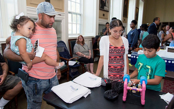 08/16/19 Wesley Bunnell | Staff TRIO, a two week long summer program run by CCSU in science and arts held their closing ceremony on Friday August 16, 2019 at Founders Hall at CCSU. Jazmarie Santiago, 3rd L, a rising 8th grade student at Pulaski Middle School, demonstrates her underwater robotics project as her father Ferdinand Santiago looks on.