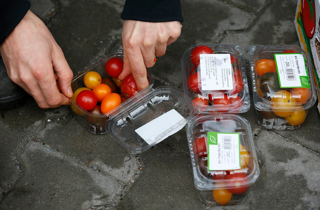 . Raphael Fellmer, a supporter of the foodsharing movement sorts out tomatoes from waste bins at the parking lot of an organic supermarket in Berlin, January 31, 2013. Foodsharing is a German internet based platform where individuals, retailers or producers have the possibility of offering surplus food to consumers for free. Picture taken January 31.  REUTERS/Fabrizio Bensch