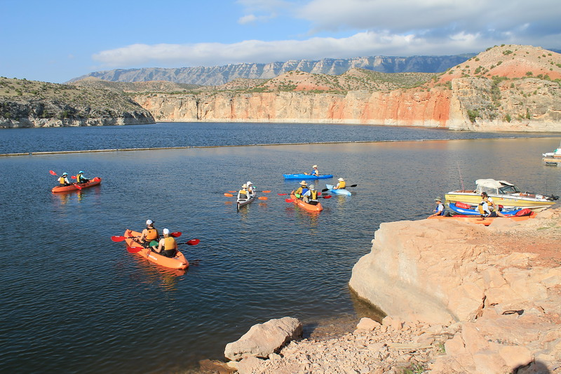 People kayaking in water surrounded by rocky cliffs at Bighorn Canyon