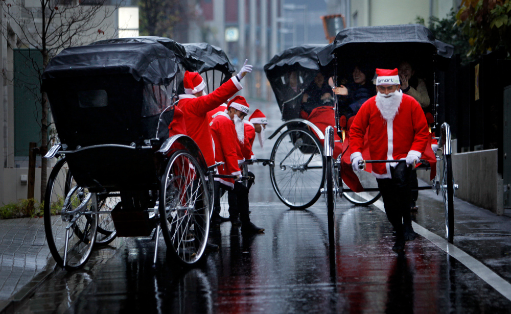 . Rickshaw drivers dressed in Santa Claus costumes transport customers in Tokyo, Japan, Thursday, Dec. 3, 2009. The drivers rode customers through the streets of Tokyo as part of a one-day promotional event hosted by French leisure intermediation company Smart&Co.  (AP Photo/Junji Kurokawa)