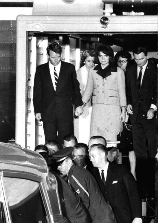 . First Lady Jacqueline Kennedy, her dress stained with blood, stands with Attorney General Robert F. Kennedy, holding her hand, as they watch the casket of her slain husband, President John F. Kennedy, placed in an ambulance at Andrews Air Force Base, Md., near Washington, November 22, 1963.  The body of the president was flown from Dallas, Texas, where he was fatally shot earlier in the day.  At right are Evelyn Lincoln, glasses, and Kenneth O\'Donnell of the White House staff.  Mrs. Lincoln was the late president\'s personal secretary.  (AP Photo)