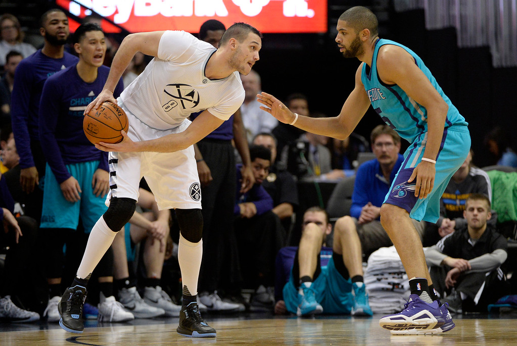 . Nicolas Batum (5) of the Charlotte Hornets defends Danilo Gallinari (8) of the Denver Nuggets during the third quarter of the Nuggets\' 95-92 win. The Denver Nuggets hosted the Charlotte Hornets at the Pepsi Center on Sunday, January 10, 2016. (Photo by AAron Ontiveroz/The Denver Post)