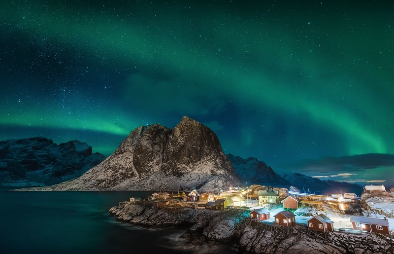 Green lights decorate the sky over a coastal village on a Northern Lights cruise.
