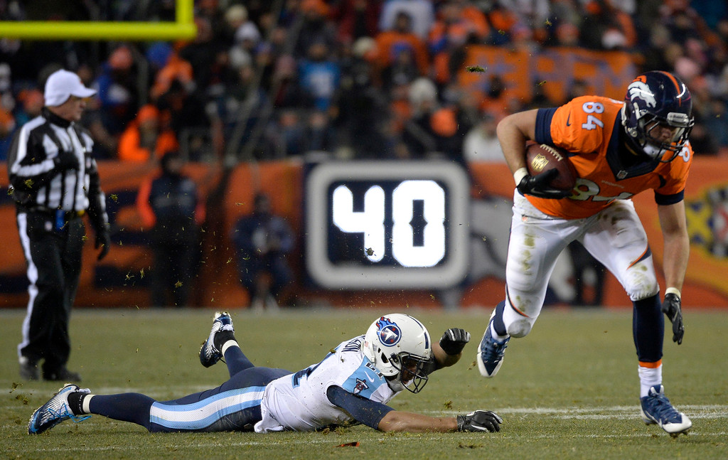 . Denver Broncos tight end Jacob Tamme (84) runs away from a missed tackle by Tennessee Titans free safety George Wilson (21) during the fourth quarter. (Photo by Joe Amon/The Denver Post)