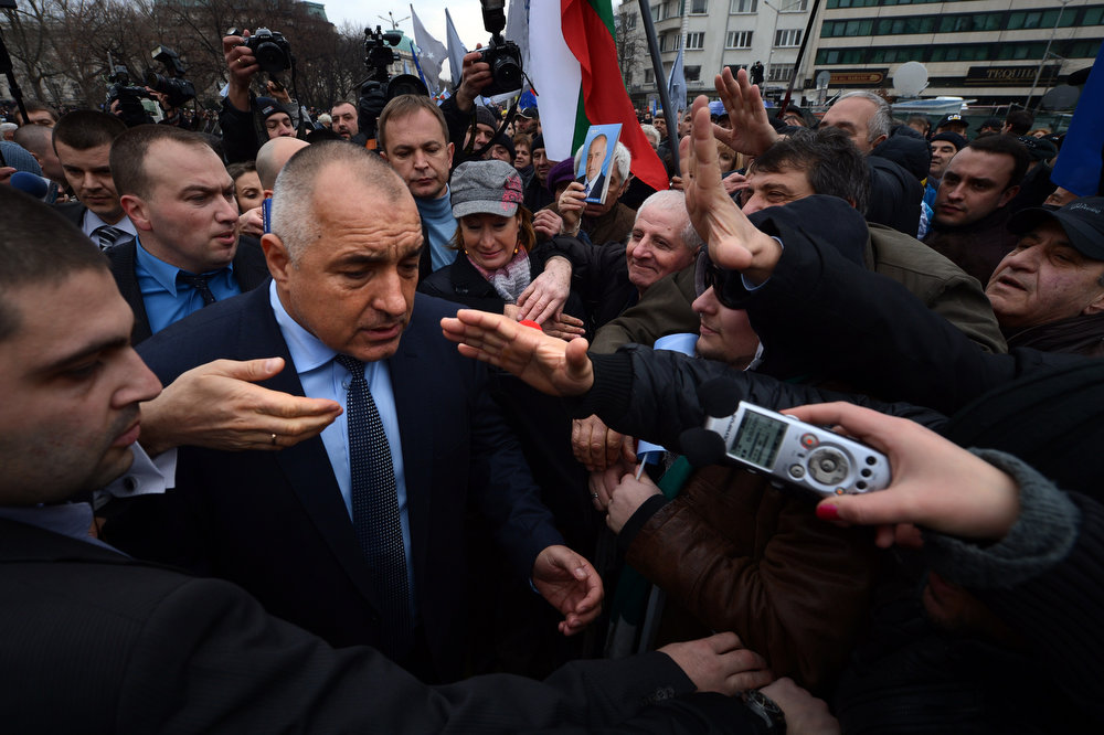 Description of . Bulgarian Prime Minister Boyko Borisov (L) greets his supporters in front of the Parliament building in Sofia on February 21, 2013. Bulgaria's parliament accepted Thursday the resignation of Prime Minister Boyko Borisov's government after days of sometimes violent protests against high electricity bills and low incomes in the EU's poorest country.  DIMITAR DILKOFF/AFP/Getty Images