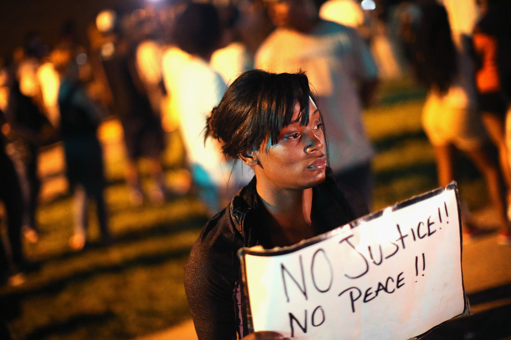 . ST. LOUIS, MO - AUGUST 12:  Demonstrators protest the killing of teenager Michael Brown outside Greater St. Marks Family Church while Browns family along with civil rights leader Rev. Al Sharpton and a capacity crowd of guests met inside to discuss the killing on August 12, 2014 in St Louis, Missouri. Brown was shot and killed by a police officer on Saturday in the nearby suburb of Ferguson. Ferguson has experienced two days of violent protests since the killing but, tonight the town remained mostly peaceful.  (Photo by Scott Olson/Getty Images)