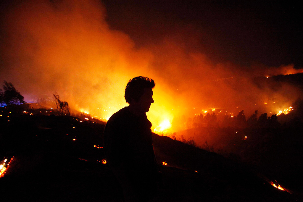. A person tries to extinguish flames during a forest fire in Valparaiso, Chile, Sunday April 13, 2014. Authorities say the fires have destroyed hundreds of homes, forced the evacuation of thousands and claimed the lives of at least seven people.  ( AP Photo/ Luis Hidalgo)