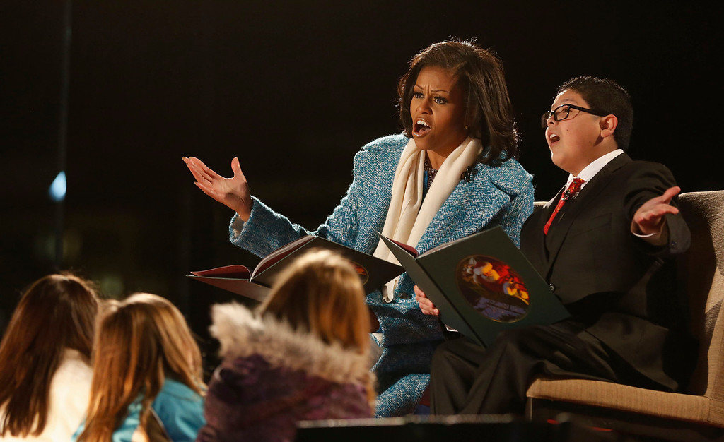 . First lady Michelle Obama and actor Rico Rodriguez (R) read a Christmas carol to children at the official lighting of the National Christmas Tree ceremony on the Ellipse in Washington, December 6, 2012.     REUTERS/Larry Downing