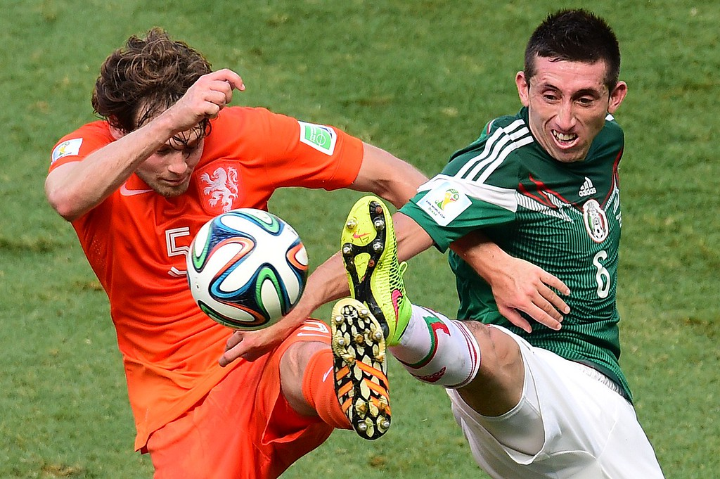 . Netherlands\' defender Daley Blind (L) vies with Mexico\'s midfielder Hector Herrera during a Round of 16 football match between Netherlands and Mexico at Castelao Stadium in Fortaleza during the 2014 FIFA World Cup on June 29, 2014.   AFP PHOTO/ JAVIER SORIANOJ