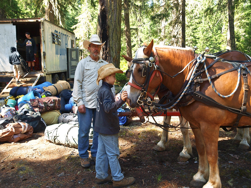 Part of a Swampers job is to stand by the team when the wagon is idle to keep the animals from walking off (and to supervise the youth wanting to pet them of course).  Swamper Chuck Wiren watches the team of Joyce Sharp's wagon.
