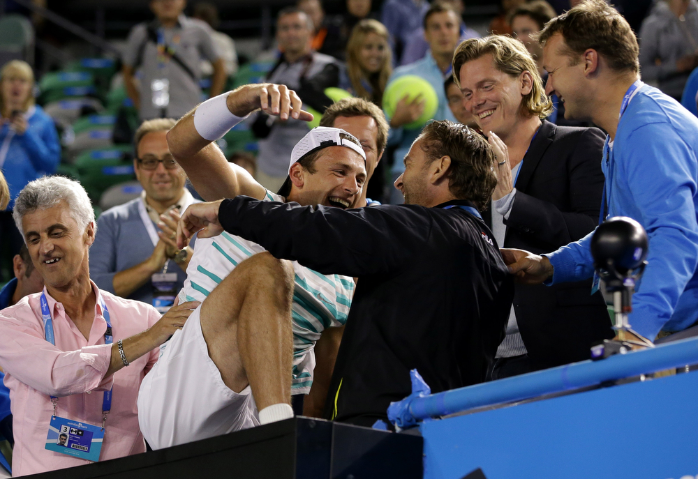 . Lukasz Kubot of Poland, center, celebrates with support team members after he and Robert Lindstedt of Sweden defeated Eric Butorac of the U.S. and Raven Klaasen of South Africa in their men\'s doubles final at the Australian Open tennis championship in Melbourne, Australia, Saturday, Jan. 25, 2014.(AP Photo/Aaron Favila)