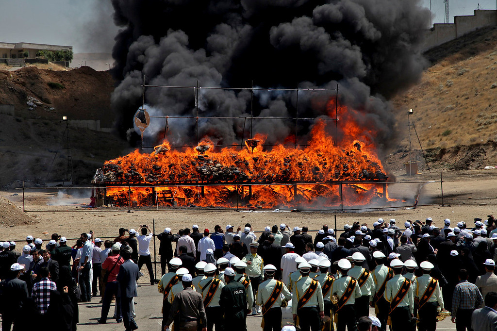 . A pile of seized narcotics is set on fire during a ceremony commemorating International Day Against Drug Abuse and Illicit Trafficking in north Tehran, Iran, Wednesday, June 26, 2013. Iran has burned at least 100 tons of illicit drugs as part of its efforts to fight drug smuggling. Iranian authorities and foreign guests watched as some 50 tons of various narcotics were burned in north Tehran at a ceremony on Wednesday to mark the UN International Day Against Drug Abuse and Illicit Trafficking. Some 50 other tons were destroyed in several other Iranian cities.  (AP Photo/Ebrahim Noroozi)