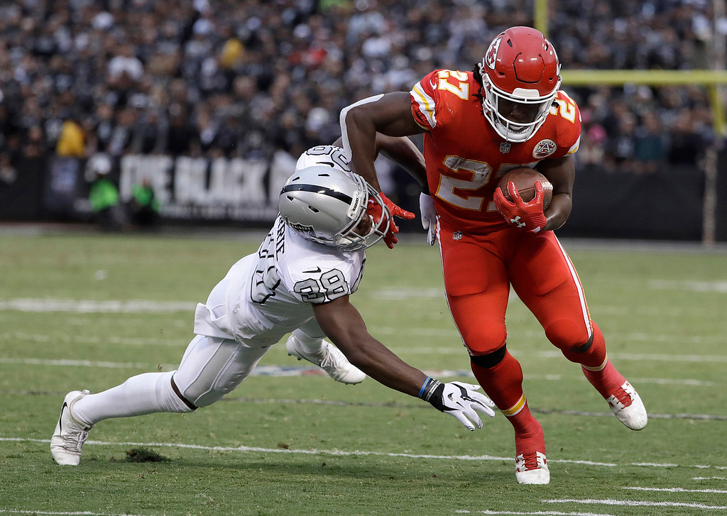 . Kansas City Chiefs running back Kareem Hunt (27) is forced out of bounds by Oakland Raiders cornerback T.J. Carrie during the first half of an NFL football game in Oakland, Calif., Thursday, Oct. 19, 2017. (AP Photo/Marcio Jose Sanchez)