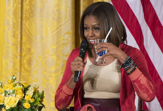 . US First Lady Michelle Obama holds up a glass of water as she encourages children to drink water as she speaks with children of Executive Office employees at the White Houses annual Take Our Daughters and Sons to Work Day in the East Room of the White House in Washington, DC, April 24, 2014. (SAUL LOEB/AFP/Getty Images)