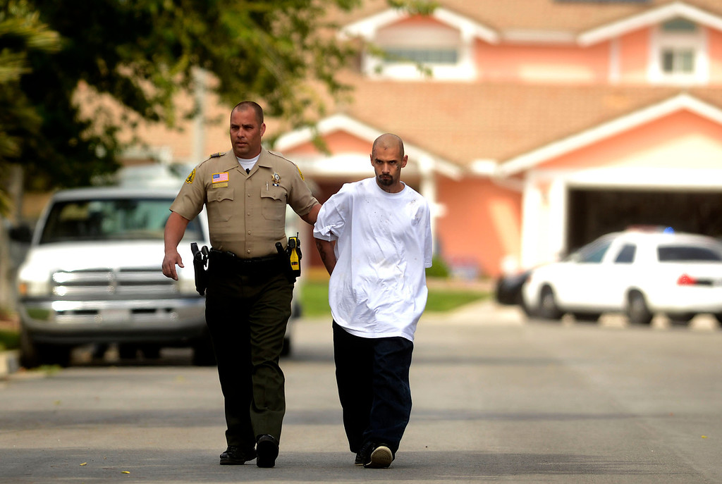. A police pursuit ends as an uninidentified man is arrested by a San Bernadino County Sheriff\'s Deputy along the 100 block of East Shamwood Avenue in Rialto April 16, 2013.  GABRIEL LUIS ACOSTA/STAFF PHOTOGRAPHER.