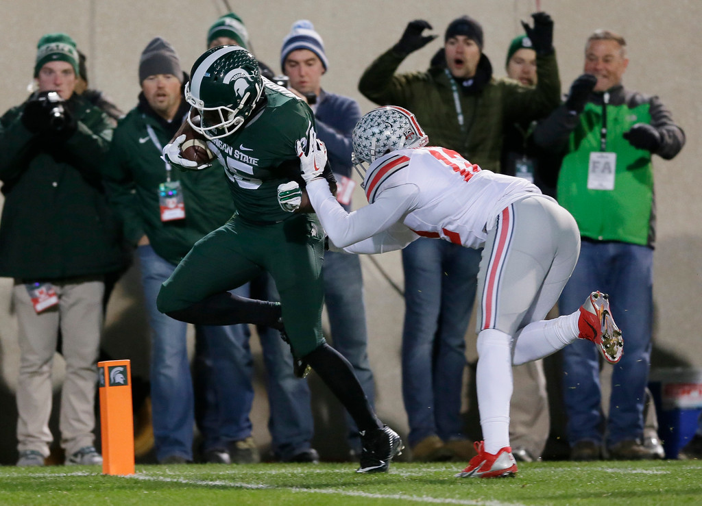 . Michigan State wide receiver Keith Mumphery (25) outruns Ohio State cornerback Doran Grant (12) for a touchdown during the first half of an NCAA college football game in East Lansing, Mich., Saturday, Nov. 8, 2014. (AP Photo/Carlos Osorio)