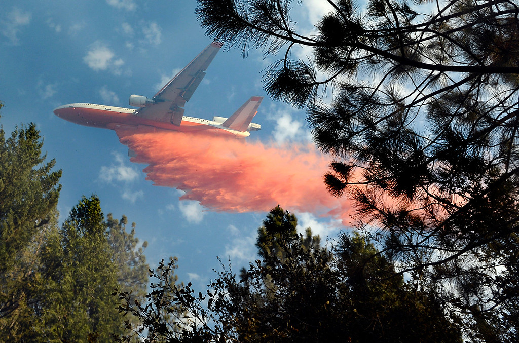 . A jet air tanker drops its load of fire retardant on a fire burning in the area of Cedar Drive in Oakhurst, Calif., Sunday, Sept. 14, 2014, as two raging wildfires in the state forced hundreds of people to evacuate their homes. The California Department of Forestry and Fire Protection said flames damaged or destroyed 21 structures. The Fresno Bee reports one neighborhood was hit especially hard, with several homes turned to ash and smoldering embers. (AP Photo/The Fresno Bee, Mark Crosse)