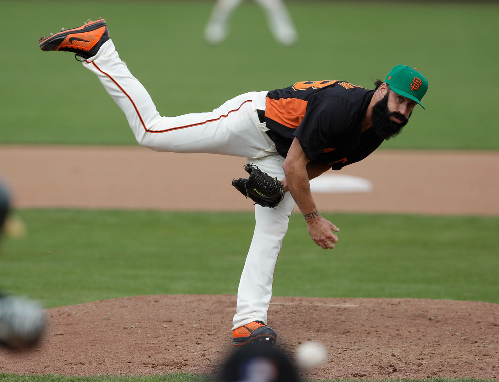. San Francisco Giants relief pitcher Brian Wilson throws to the Oakland Athletics during the seventh inning of a spring training baseball game Saturday, March 17, 2012 in Scottsdale, Ariz. (AP Photo/Marcio Jose Sanchez)