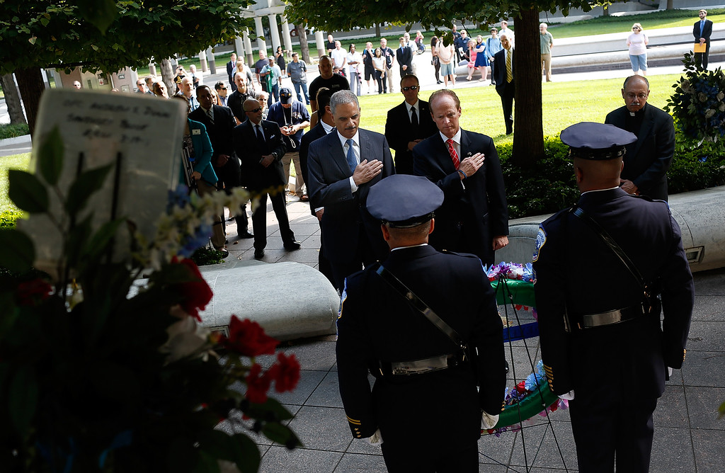 . U.S. Attorney General Eric Holder (L) and Craig Floyd (R), Chairman of the National Law Enforcement Officers Memorial Fund, place their hands over their heart during a moment of silence at the National Law Enforcement Memorial on the 13th anniversary of the September 11th attacks September 11, 2014 in Washington, DC. 72 law enforcement officers died in the line of duty on September 11, 2001, more than on any other day in American history.  (Photo by Win McNamee/Getty Images)