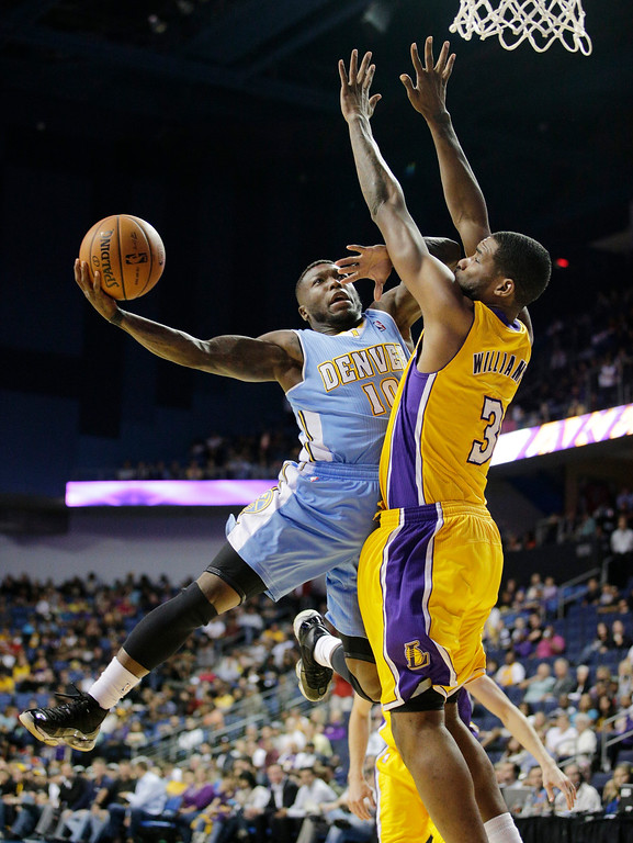. Denver Nuggets\' Nate Robinson, left, puts up a shot against Los Angeles Lakers\' Shawne Williams in the second half of an NBA preseason basketball game on Tuesday, Oct. 8, 2013, in Ontario, Calif. The Lakers won 90-88. (AP Photo/Jae C. Hong)