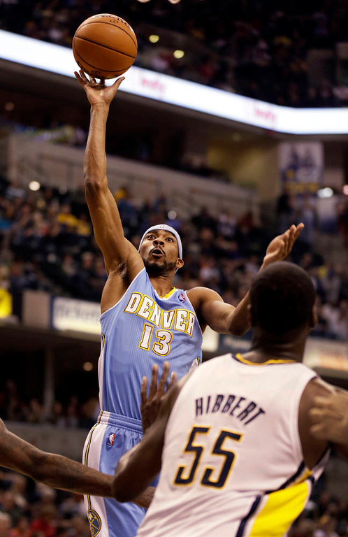 . Denver Nuggets small forward Corey Brewer, left, shoots over Indiana Pacers center Roy Hibbert during the first half of an NBA basketball game , in Indianapolis, Friday, Dec. 7, 2012. The Nuggets won 92-89. (AP Photo/AJ Mast)