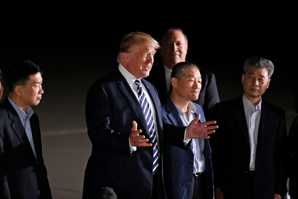 . President Donald Trump, accompanied by Secretary of State Mike Pompeo, back, talks after greeting former North Korean detainees Tony Kim, left, Kim Dong Chul, and Kim Hak Song, right, upon their arrival, Thursday, May 10, 2018, at Andrews Air Force Base, Md. (AP Photo/Alex Brandon)