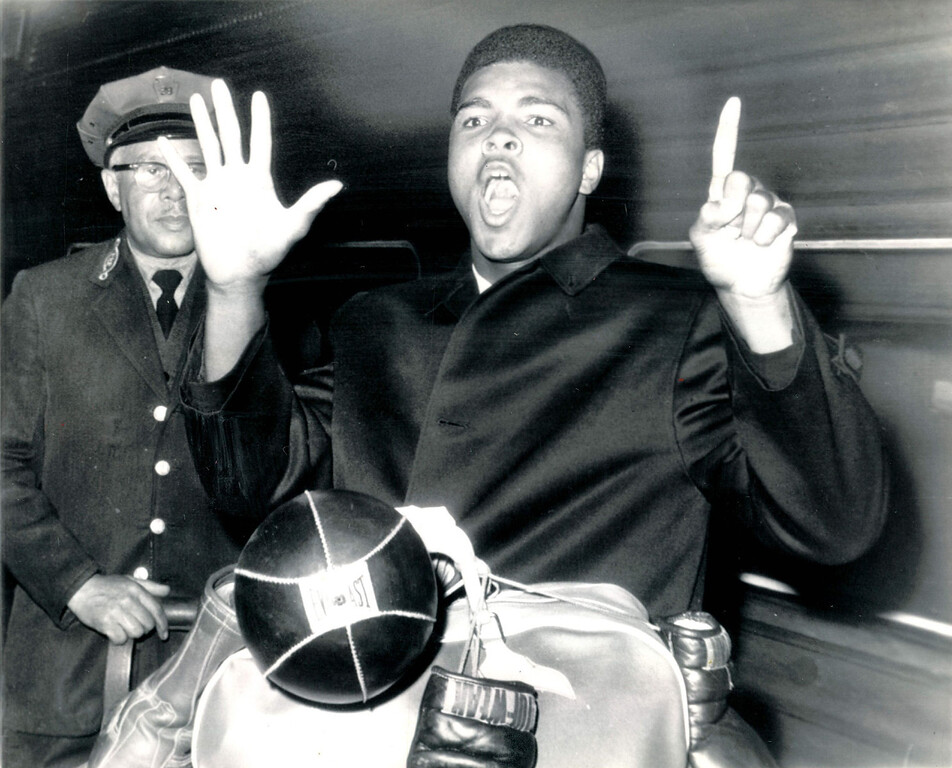 """. Cassius Clay, brash young heavyweight, holds up six fingers to denote the round in which he expects to demolish Doug Jones when they tangle in Madison Square Garden Wednesday.  Clay arrived in New York from Miami where he spent much of his time needling Sonny Liston.  Jones\' response to Clay\'s latest poems.  \""""What did he say?\""""  1963. Denver Post Library photo archive"""
