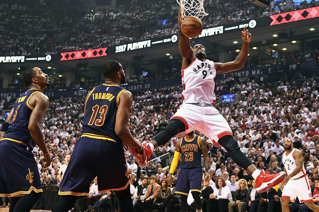 . Toronto Raptors forward Serge Ibaka (9) dunks as Cleveland Cavaliers guard JR Smith (5) and center Tristan Thompson (13) look on during the first half of Game 3 of an NBA basketball second-round playoff series in Toronto on Friday, May 5, 2017. (Frank Gunn/The Canadian Press via AP)