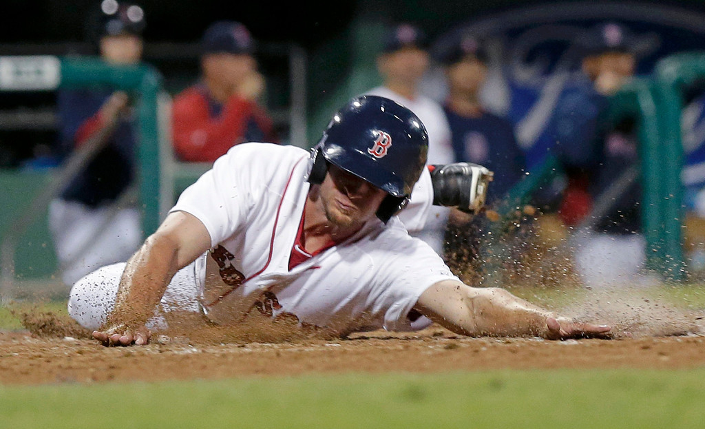 . Boston Red Sox Jonathan Roof reaches home on an RBI double by Mike McCoy in the eighth inning. (AP Photo/Gerald Herbert)