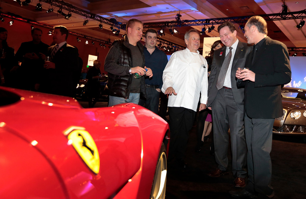 . Chef Wolfgang Puck, third right, stands next to a red Ferrari SpA F12 at The Gallery in the MGM Grand Detroit ahead of the 2013 North American International Auto Show (NAIAS) in Detroit, Michigan, U.S., on Saturday, Jan. 12, 2013. The Detroit auto show runs through Jan. 27 and will display over 500 vehicles, representing the most innovative designs in the world. Photographer: Jeff Kowalsky/Bloomberg   *** Local Caption *** Wolfgang Puck
