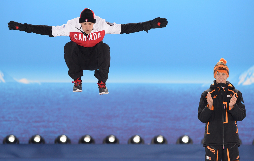 . A picture taken with a robotic camera shows (from L) Canada\'s silver medalist Denny Morrison jumping next to Netherlands\' gold medalist Stefan Groothuis during the Men\'s Speed Skating 1000 m Medal Ceremony at the Sochi medals plaza during the Sochi Winter Olympics on February 13, 2014.  ANTONIN THUILLIER/AFP/Getty Images